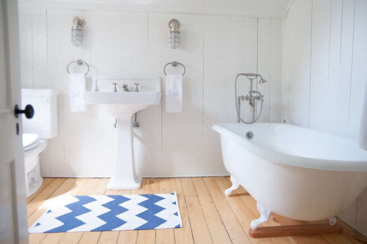 Stripes gone haywire: InBefore & After: A Summer Cottage Reborn on the Connecticut Coast,a chevron mat plays onthe classicblue-and-white-striped cottage rug.