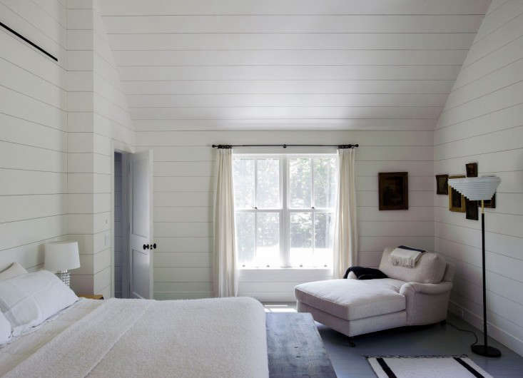 In this bedroom, designer Tiina Laakonen ran horizontal shiplap right up the walls and ceiling. The effect is a seamless transition from wall to ceiling that emphasizes the height and the width of the room. Note also that the curtains are pushed to the side to frame the view. Photograph by Matthew Williams from Remodelista: A Manual for the Considered Home.