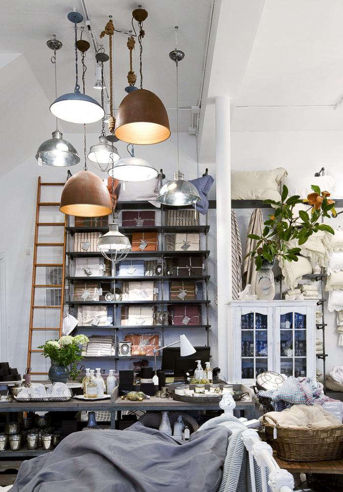Above: Industrial Lighting From H. D. Buttercup Hangs Above A Table  Displaying A Collection Of Goods Ranging From Candles, Incense, And Body  Wash With ...