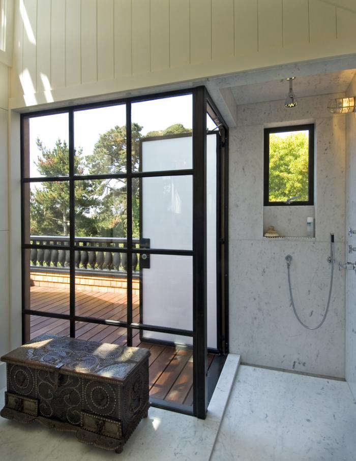 A marble-clad shower with an obscure-glass (frosted) door that opens
