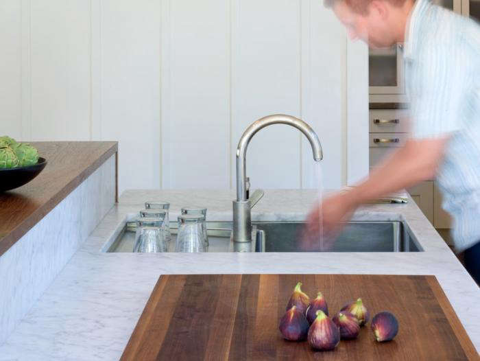 In this Indoor/Outdoor Kitchen, Buttrick created a custom stainless drain board behind the sink, which frees up the area on either side. The marble recessed backsplash is built into the raised walnut counter that sits six inches taller than the marble counter, concealing the work area from guests but still making it visually gratifying for guests on the other side.