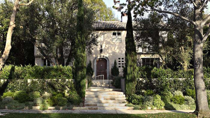 Provence style home in Brentwood with cypress trees, stone, and arched door. #provence #frenchcountry #homeexterior