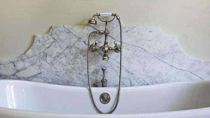 Detail of decorative marble backsplash for bathtub in luxurious bathroom of Provence style home of architect William Hefner. #marble #backsplash #luxurybathroom #freestandingtub