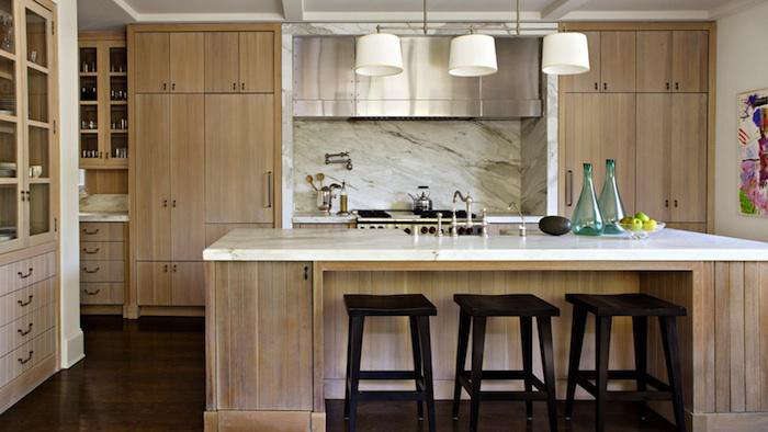 Beautifully luxurious kitchen designed by William Hefner for his own home. White oak cabinets have a semi-transparent wash, and calacatta gold marble covers the island with breakfast bar. #kitchendesign #classic #whiteoak #calacattagold #luxurykitchen