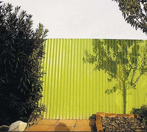 corrugated metal fence. outdoors corrugated metal fence painted green