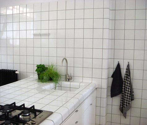 above l a tiled niche under the sink provides storage space above r in the shower block tiles serve as storage shelves for soap and shampoo