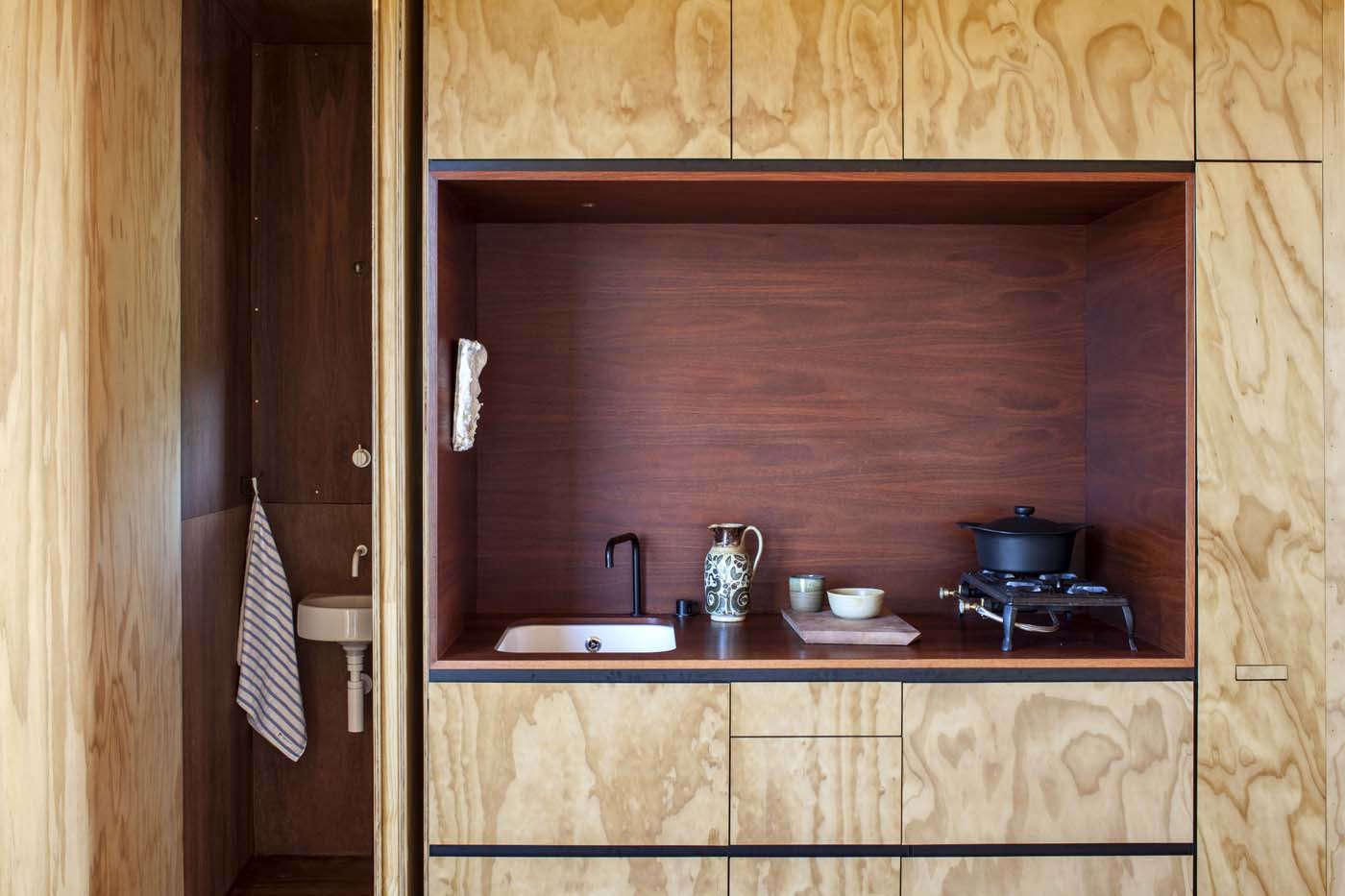 Kitchenettes in two tiny New Zealand cabins are equipped with a refrigerator and dishwasher (hidden behind panels), a small sink, and gas cooktop.