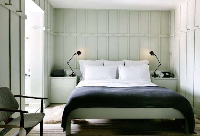 Black Jielde reading lamps flank the bed in London's High Road House; seeHigh Road House in London Gets a Revamp.