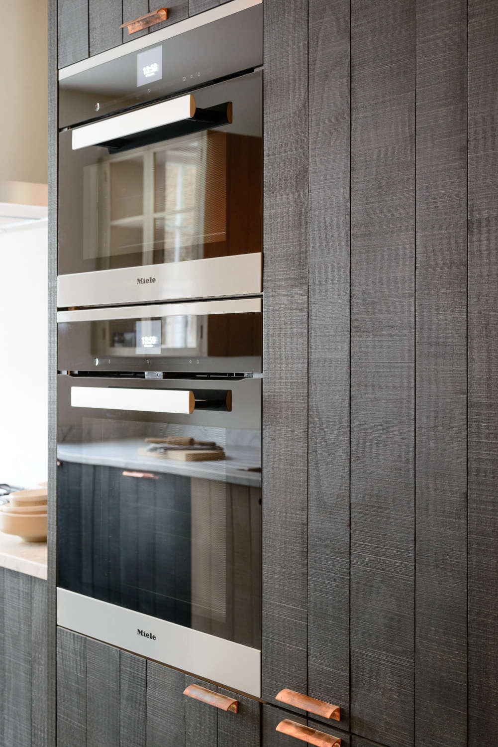 Black wood-paneling with wall oven in the Marylebone galley by DeVol   Remodelista