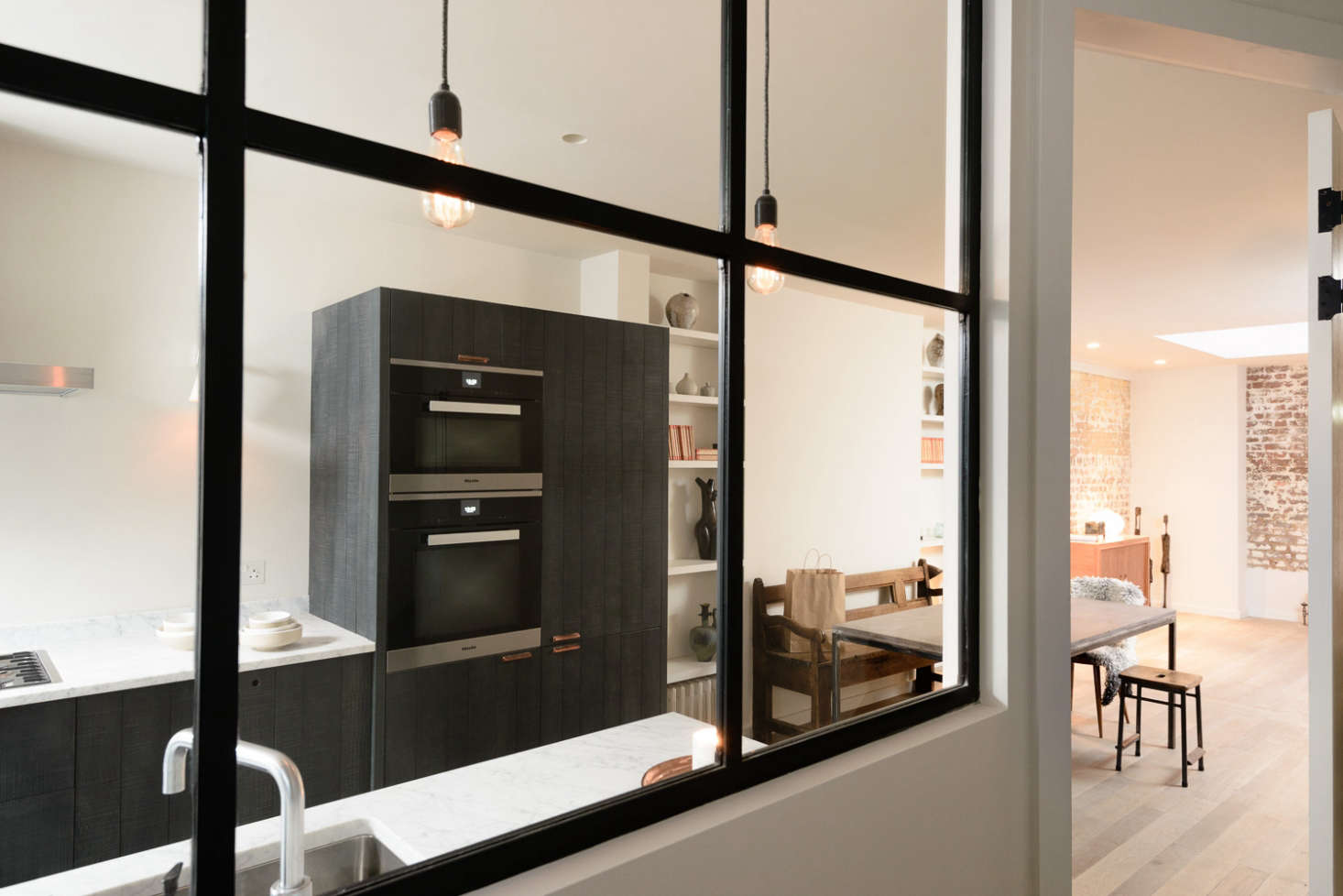 Black wood paneled cabinets and marble counters in the Marylebone kitchen by Simon Cox for DeVol   Remodelista