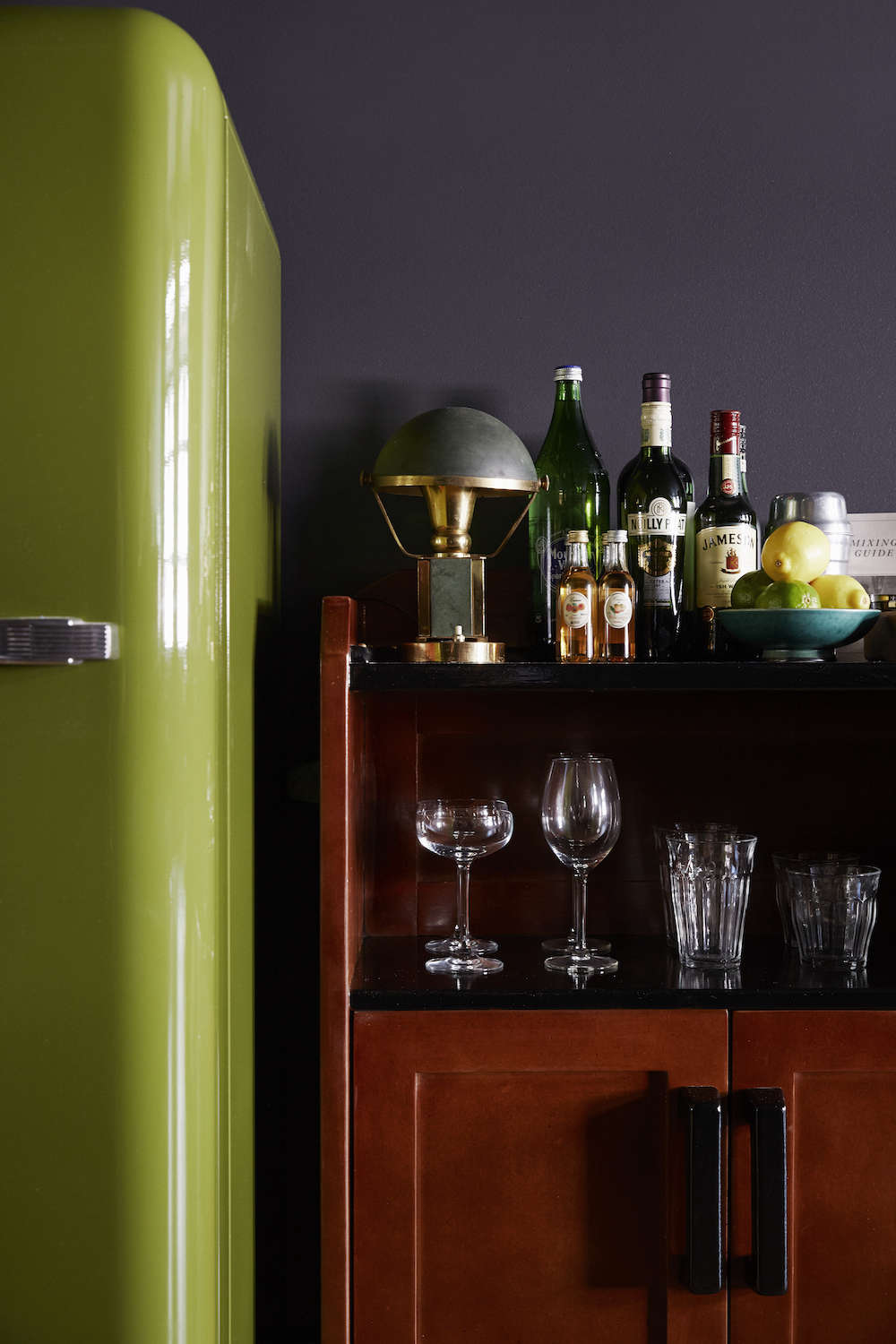 The Smeg refrigerator ina custom green color is stocked with freshcocktail essentials.