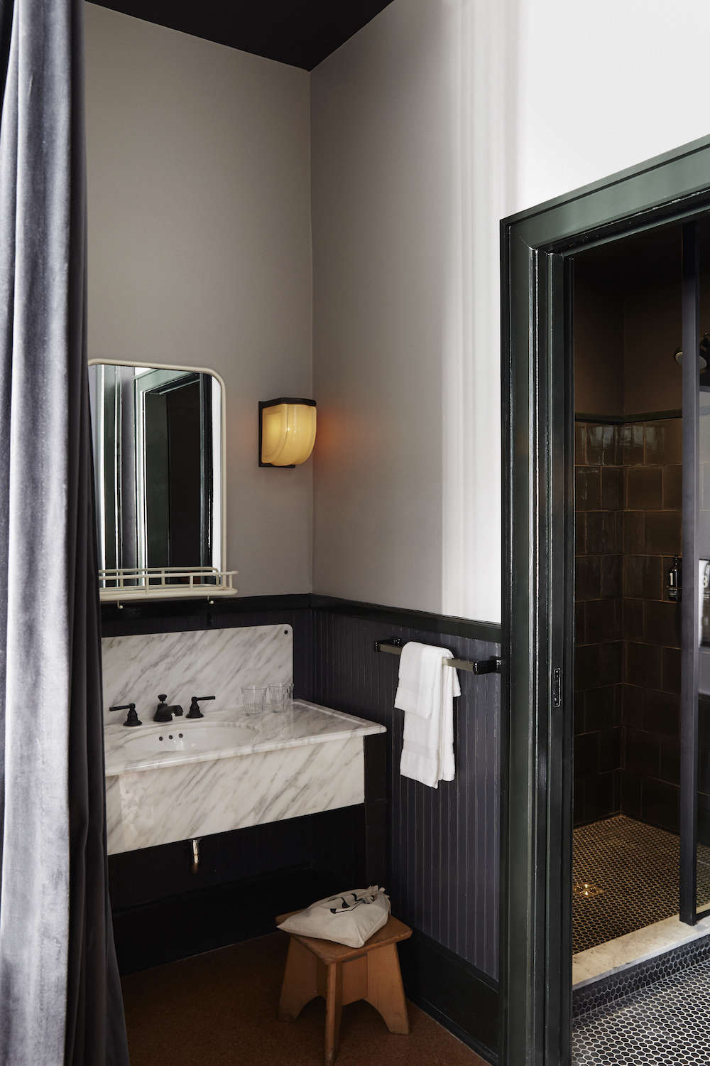 The washroom is hidden by a purple velvet curtain and features custom fixtures and lighting by Roman & Williams. The bathrooms are stocked with soap fromPearl+ and toiletries by Rudy's Barbershop.