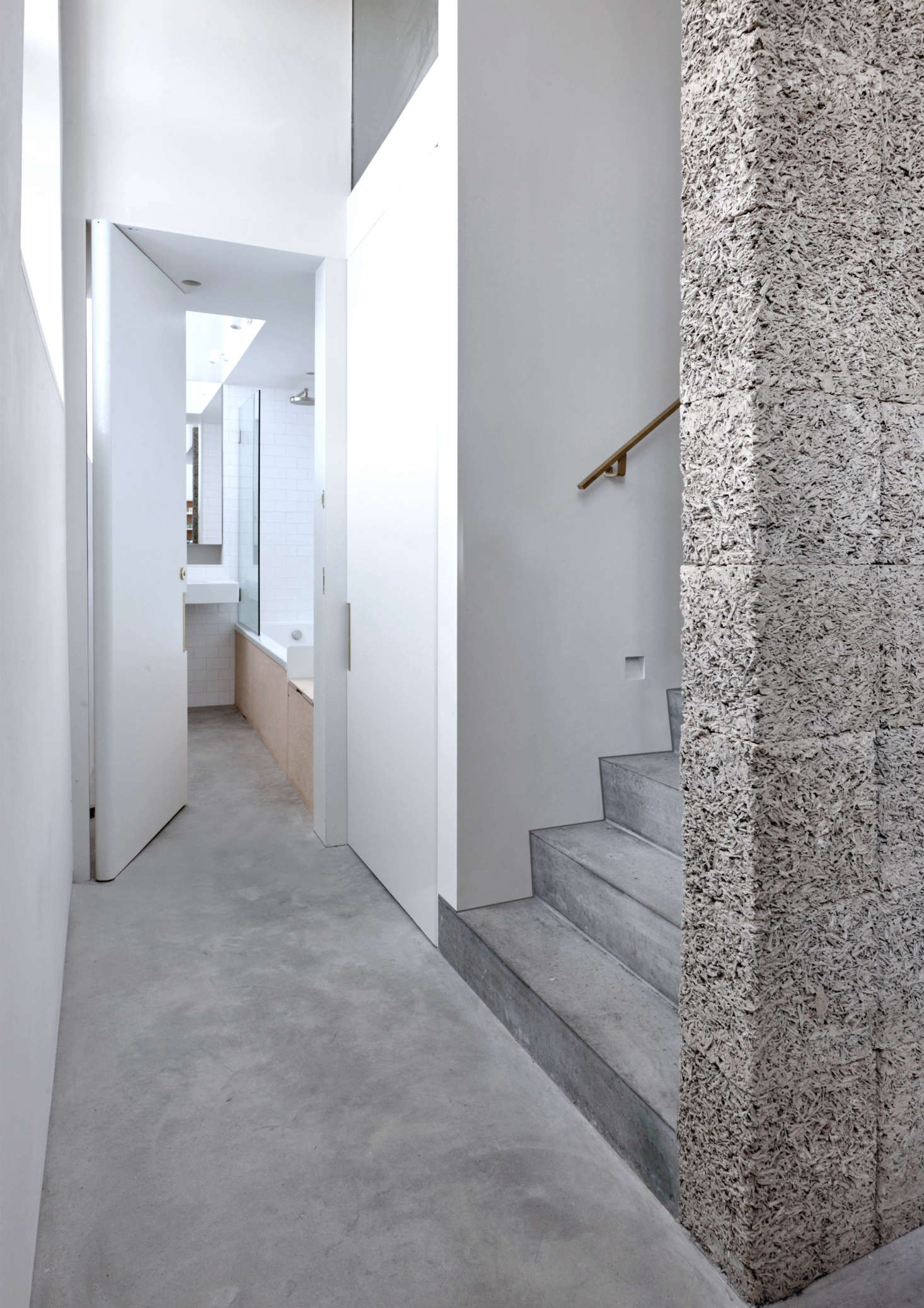 Another version of recycled wood-cementappears as the dramatic structural spine of the stairs. Also shown, a glimpse of the skylit downstairs bath, where polished concrete and plywood meet white tiles and glass.