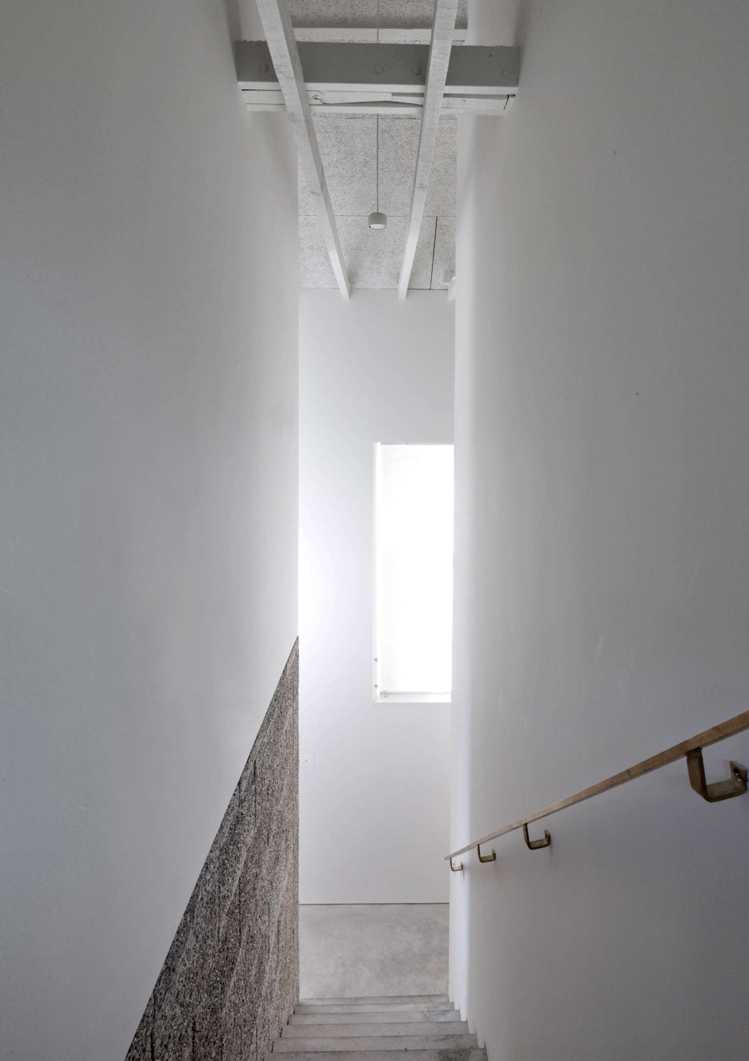 For a lighter effect, the Durisol is paired with drywall. Theelegant handrail is fabricated entirely ofbrass.