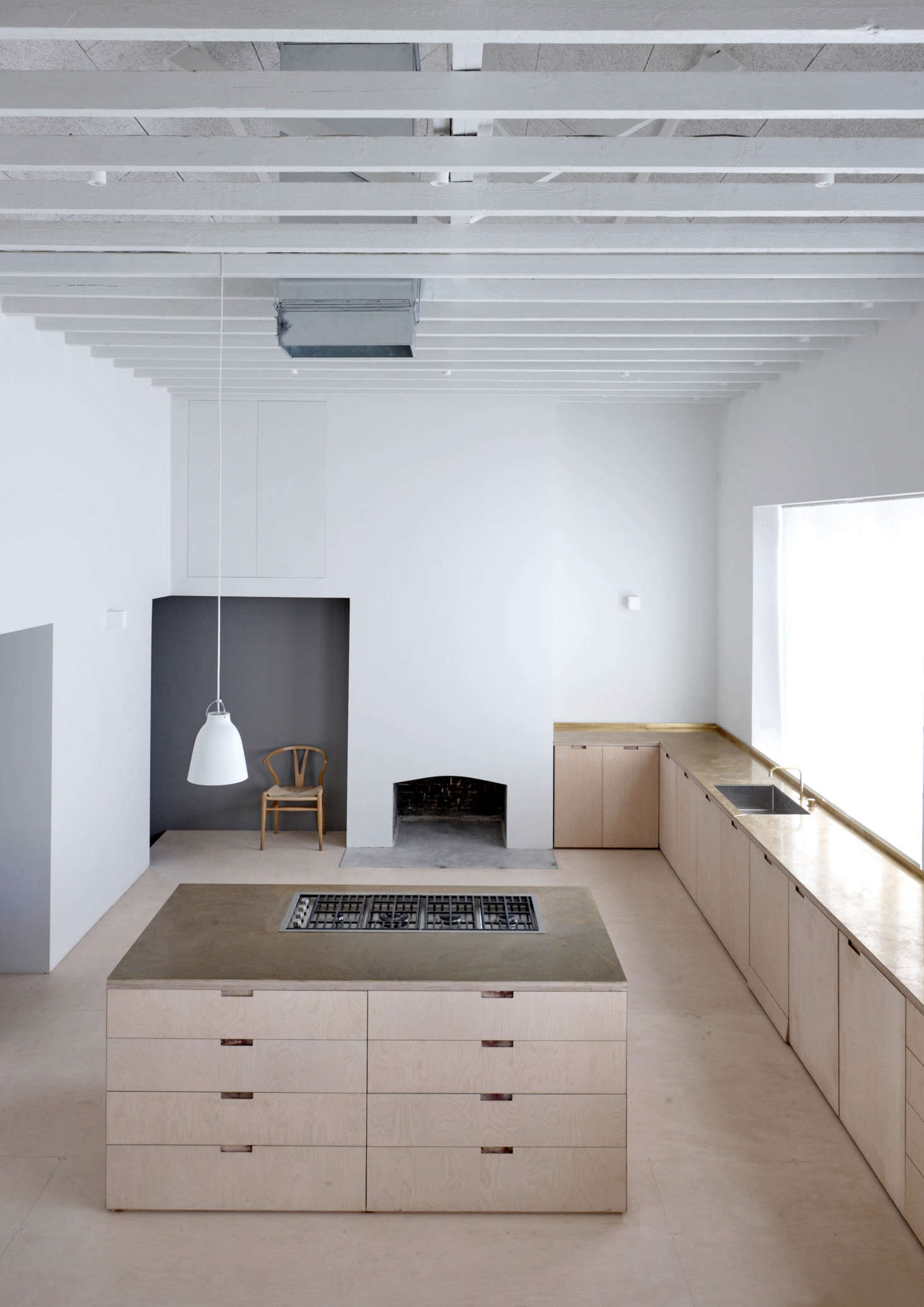 """Viewed from the upstairs bedroom, the kitchen is """"almost church-like in scale and arrangement"""" says McLaren, noting that the materials have been """"left in their natural state—'as found'—and, together with the pleasing rhythms of the original building, combine to make a building of conceptual simplicity and spatial purity."""""""