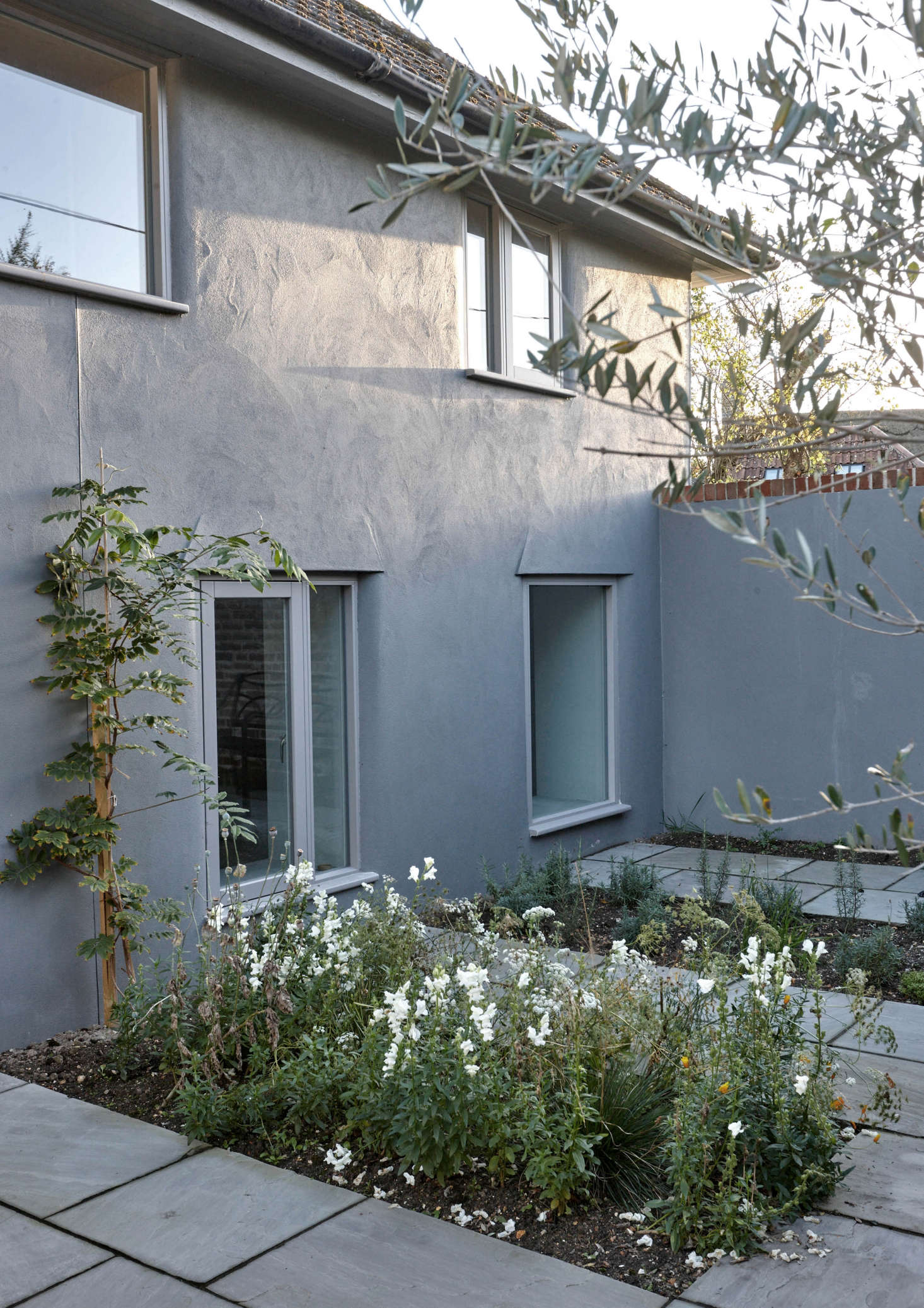 """The exterior of the old school was also overhauled. Though the roof was left as is—""""cement tiles from the 1980s, not worth focusing on,"""" says McLaren—all-new windows were introduced and the walls were lime rendered and painted, a traditional UK approach that allows the building to breathe. A slate terracewith plantingsnow leads to the front door."""