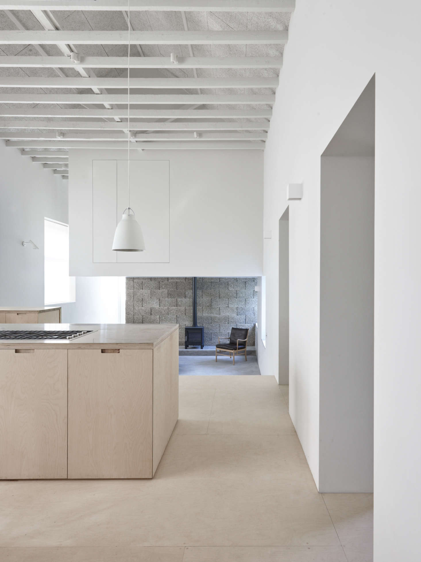 The ground floor featuresa dramatic double-height kitchen. It opens to the living room and clubhouse-like new second-story bedroom area that the architects carved out of gained and unused space—read on for trade secrets.