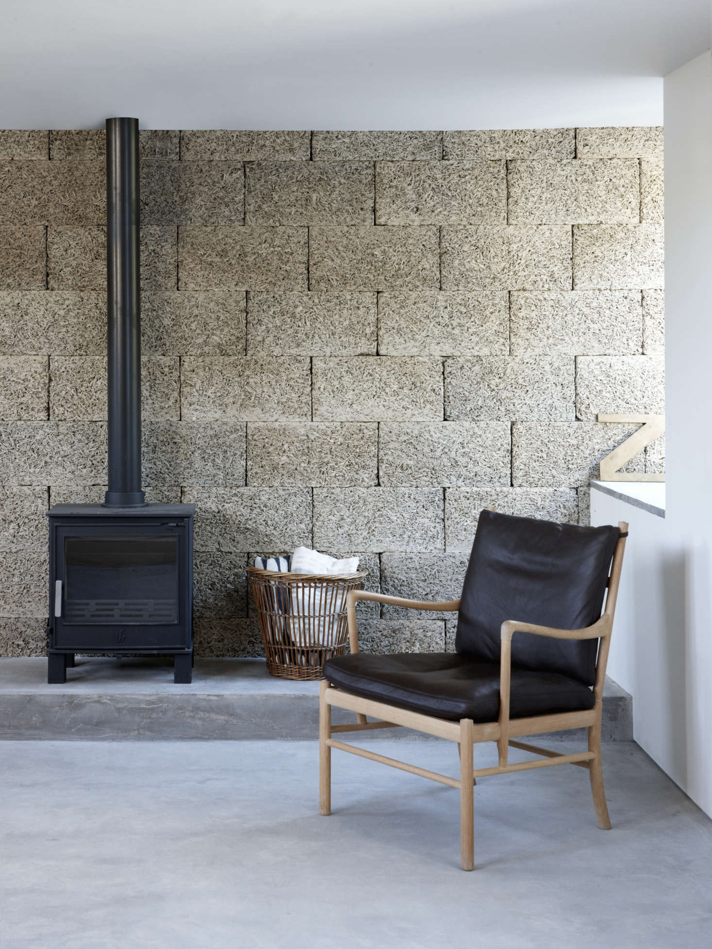 Textural wood wool blocks form the living room back wallandlend an intimacy to the space. (Also known as excelsior, these compressed strands of wood bonded with cement are traditionally used among other things as insulation.) The armchair is Ole Wanscher's 1949 149 Colonial Chair by Carl Hansen. For willow baskets similar tothis one, see Object Lessons: Almighty Wicker Basket.