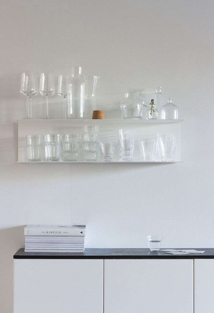Ikea bent metal shelving holds glassware. The white paint used throughoutis byFinnish lineTikkurila and is a wipeable formula made for kitchens and baths.