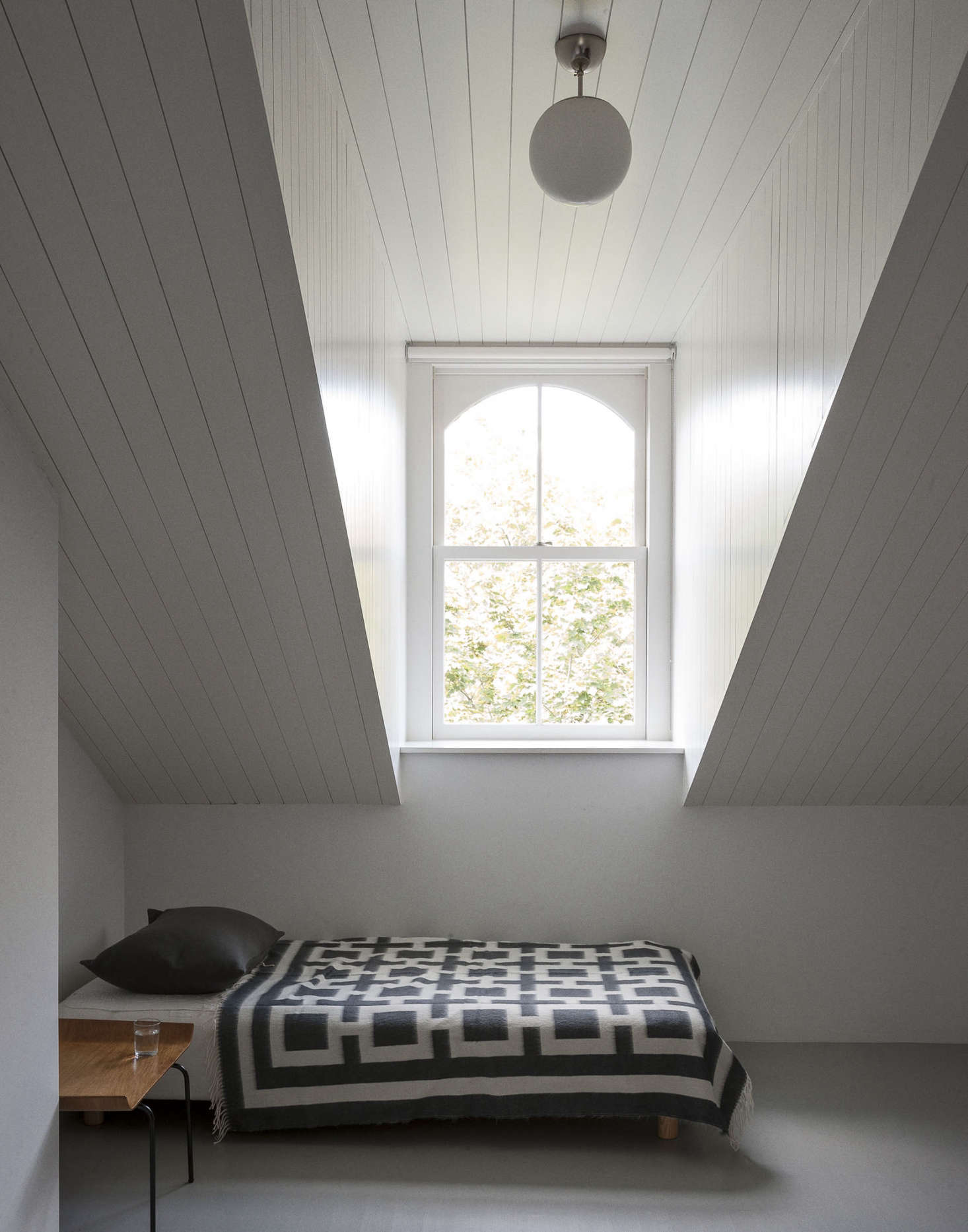 A Scandinavian wool blanket adds pattern to a streamlined attic guest room in Brooklyn. Photograph by Matthew Williams for Remodelista; see more in Nordic Beauty: A Brooklyn Townhouse Reinvented with Style—and Restraint.