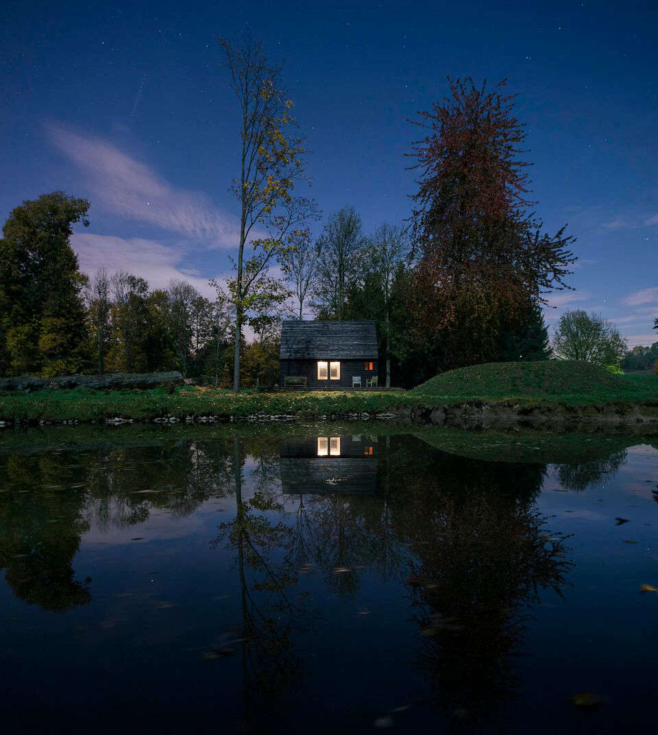 Belgian cabin at dusk designed and built by London architecture firm De Rosee Sa Architects | Remodelista