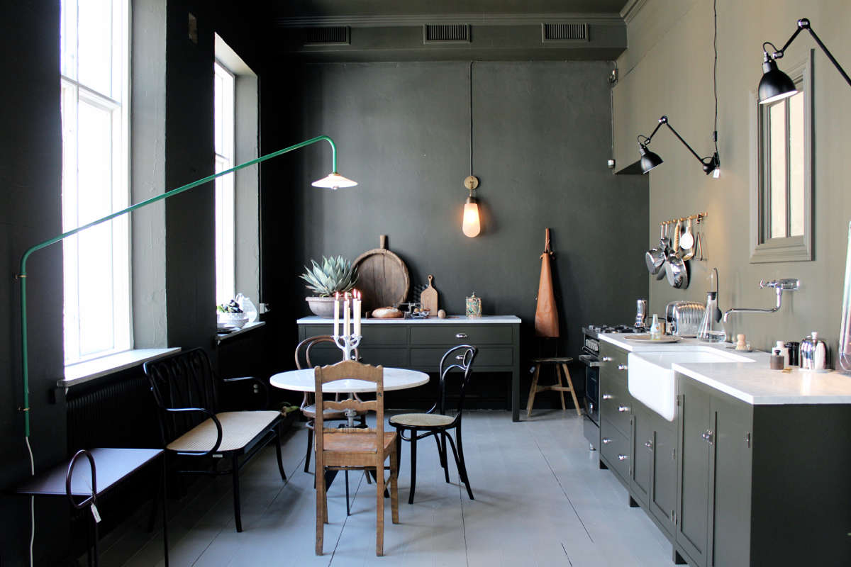 In a 2016 pop-up apartment designed by Gothenburg design shop Artilleriet, the kitchen featured mismatched dining chairs, Lampe Gras lights, and a cohesive backdrop of dark green. See the rest of the space in Master Mix: A Shoppable Apartment in Gothenburg, Sweden. Photograph by Johanna Bradford, courtesy of Artilleriet.