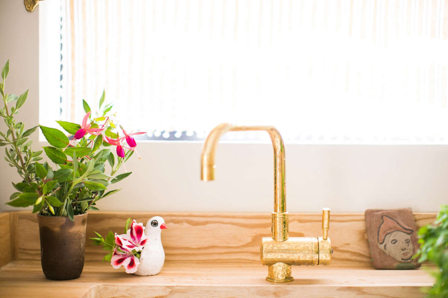 The couple chose brass and bronze fittings throughout the room for a warm glow. The countertop is fabricated from ash wood, sealed with linseed oil.