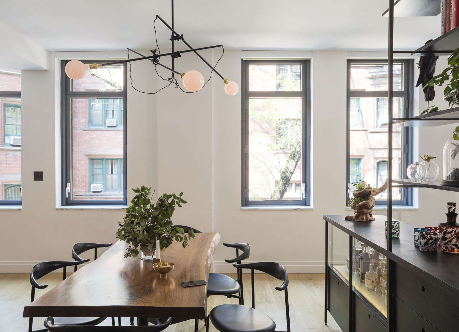 Live-edge oak dining table and Workstead industrial chandelier in an apartment remodel by Workstead, Matthew Williams photo | Remodelista