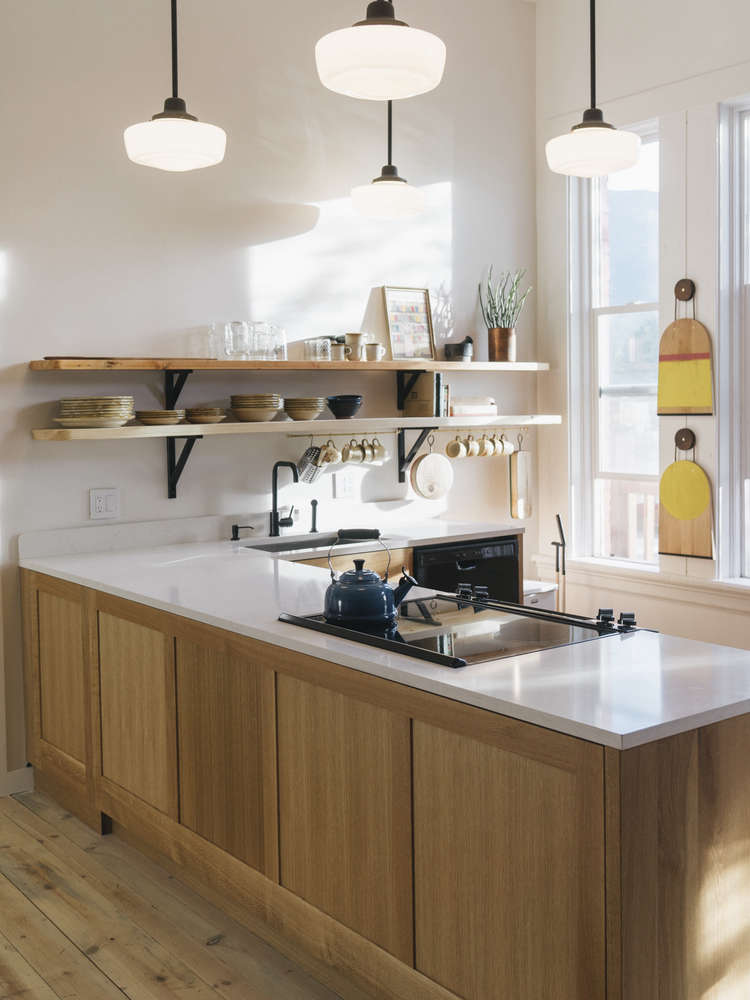 Thekitchen is anchored bycustom oak cabinets by Phloem Studio, topped with quartz countertops. On the back wall are two Hand-Painted Yellow Cutting Boards by M. Crow & Co., suspended from oxidized cherry hanging pucks withleather cord.