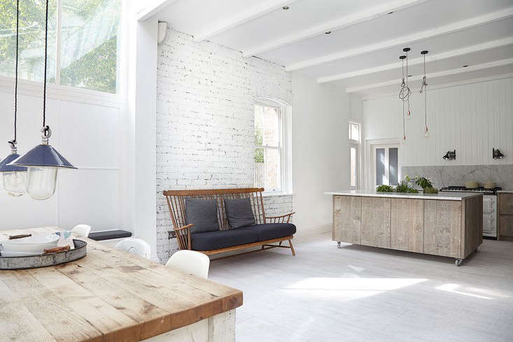 "The open kitchen is fronted by a marble-topped island built from wood textured to look like reclaimed timber. ""The best way to describe the design is an exploration into textures,"" says Blake, ticking off a list of materials that includes porcelain floor tiles, beadboard paneling, subway tiles, and painted brick. Note that the designer carefully hewed to a subtly contrasting pale palette offset by dark overhead cabinets and a trough of herbs sprouting in the middle of the island. Photograph courtesy of Blakes London."