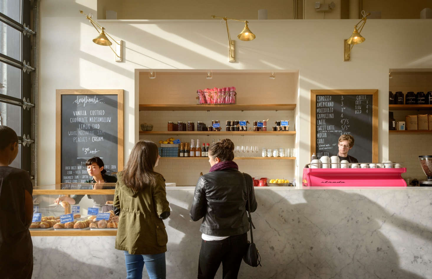 The space is a lively pink and white, anchored by a La Marzocco Strada espresso machine, custom powder-coated in pink. Custom brass light fixtures were fabricated by Chris Freed.