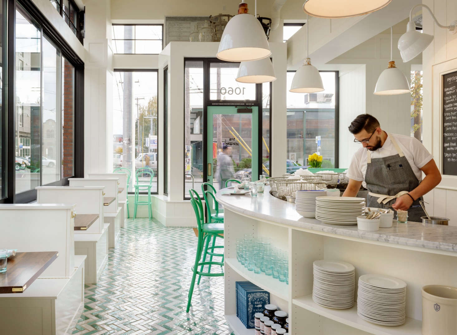 The color palette is green and white, with brass and walnut accents. The seafoam green is a nod to the menu's oceanic origins.