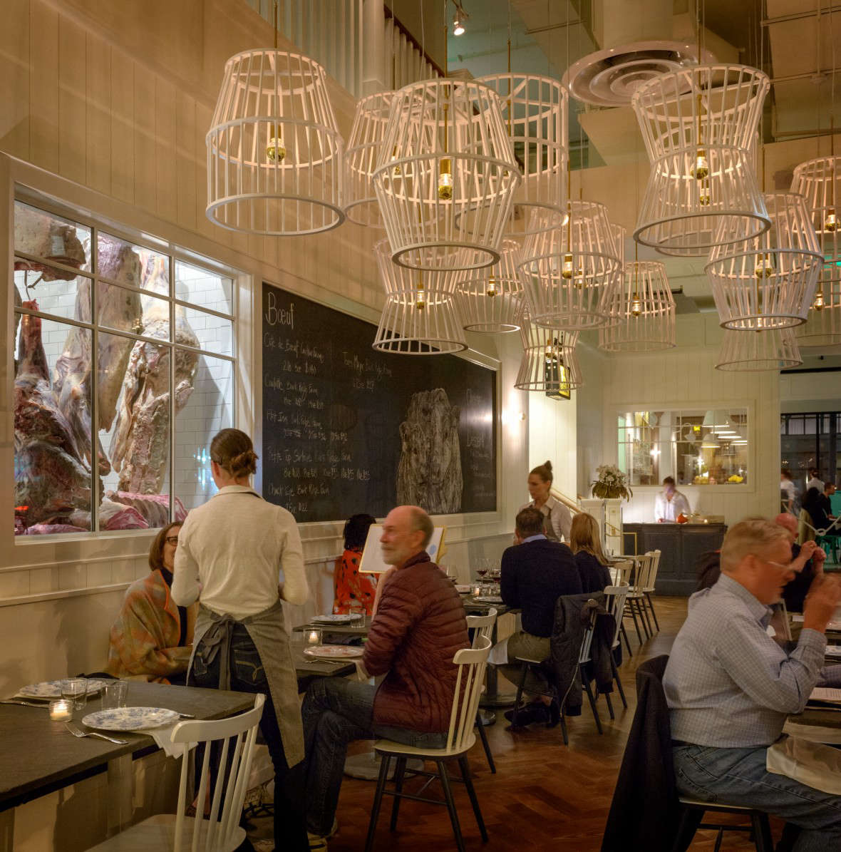 The neutral-hued restaurant features herringbone wood floors, slate-topped tables, andwhitewashed wood siding.