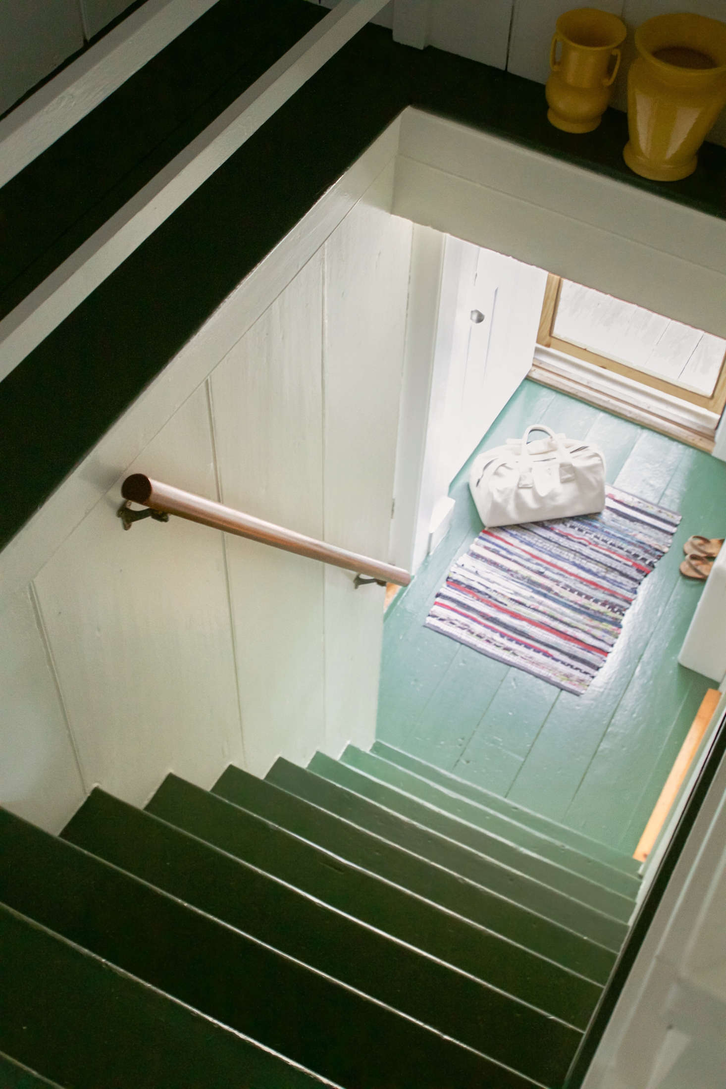 Narrow wooden stairs are painted in Benjamin Moore&#8