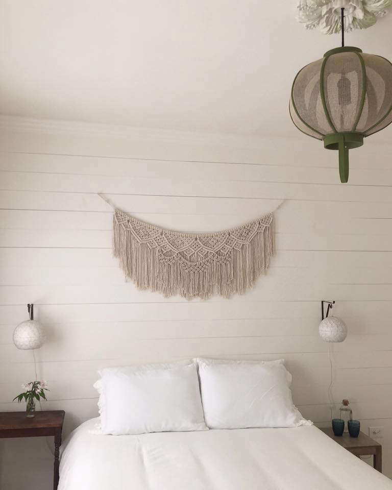 A macramé artwork hangs over one of the beds.
