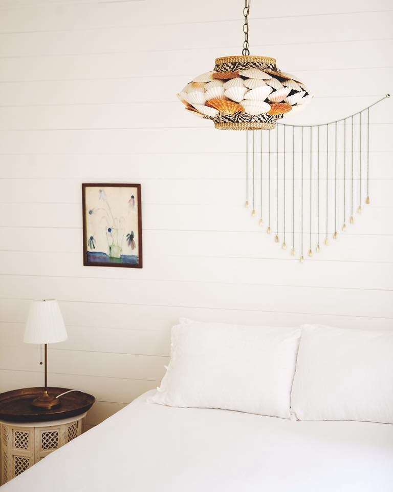 In another bedroom, a vintage seashell-encrusted lamp adds a note of kitsch.