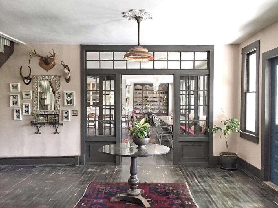 The entry hall is anchored by a round table and the walls are hung with vintage finds (framed butterflies included) that the couple has collected over the years.