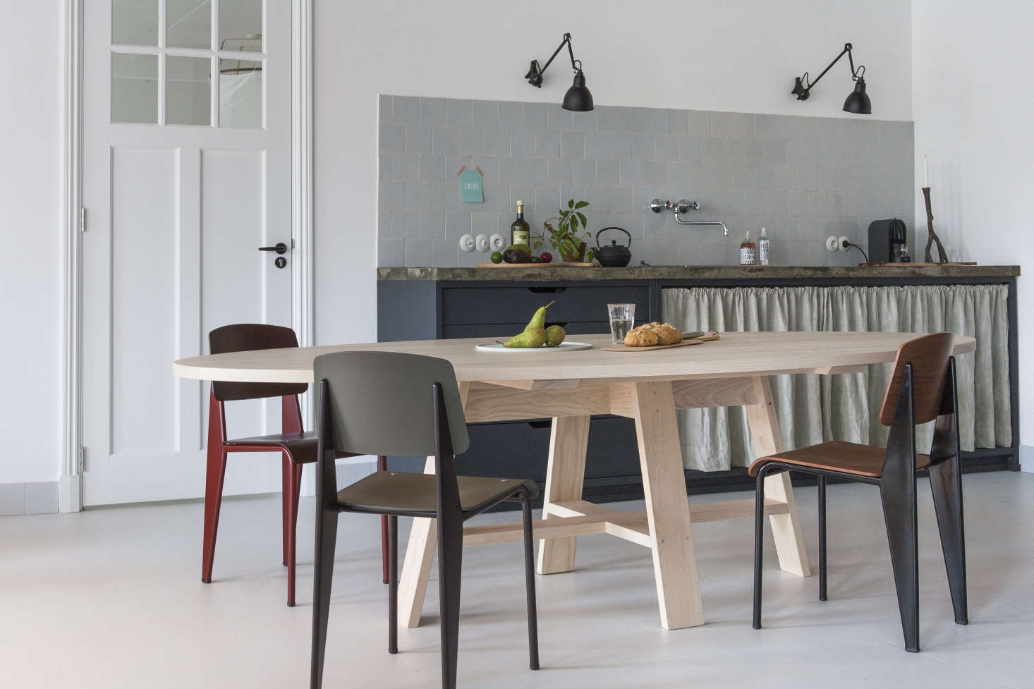 Thenew open-plan setup revolves arounda kitchen witha tight palette of white, charcoal, and pale gray offset by the pale oak of Starkenburg&#8