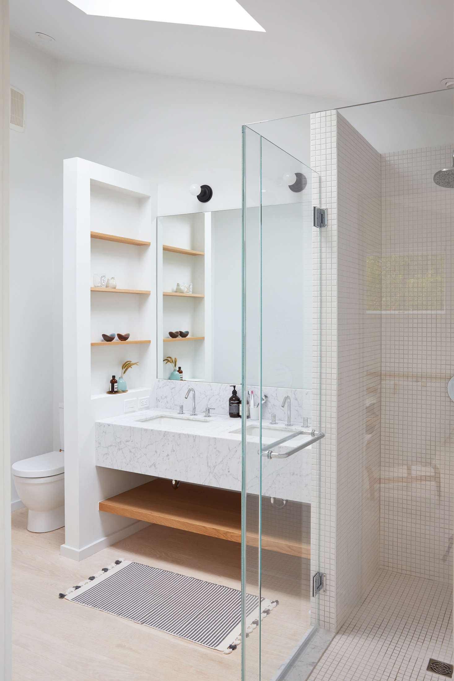In the master bedroom, a custom marble vanity (also with marble from ABC Stone in Brooklyn) is fitted with custom oak shelves, perfect for storing bath essentials. A glass-enclosed shower uses square tiles from Nemo Tile. The toilet is the Duravit Happy D., and the striped rug is from Nickey Keyhoe in LA.