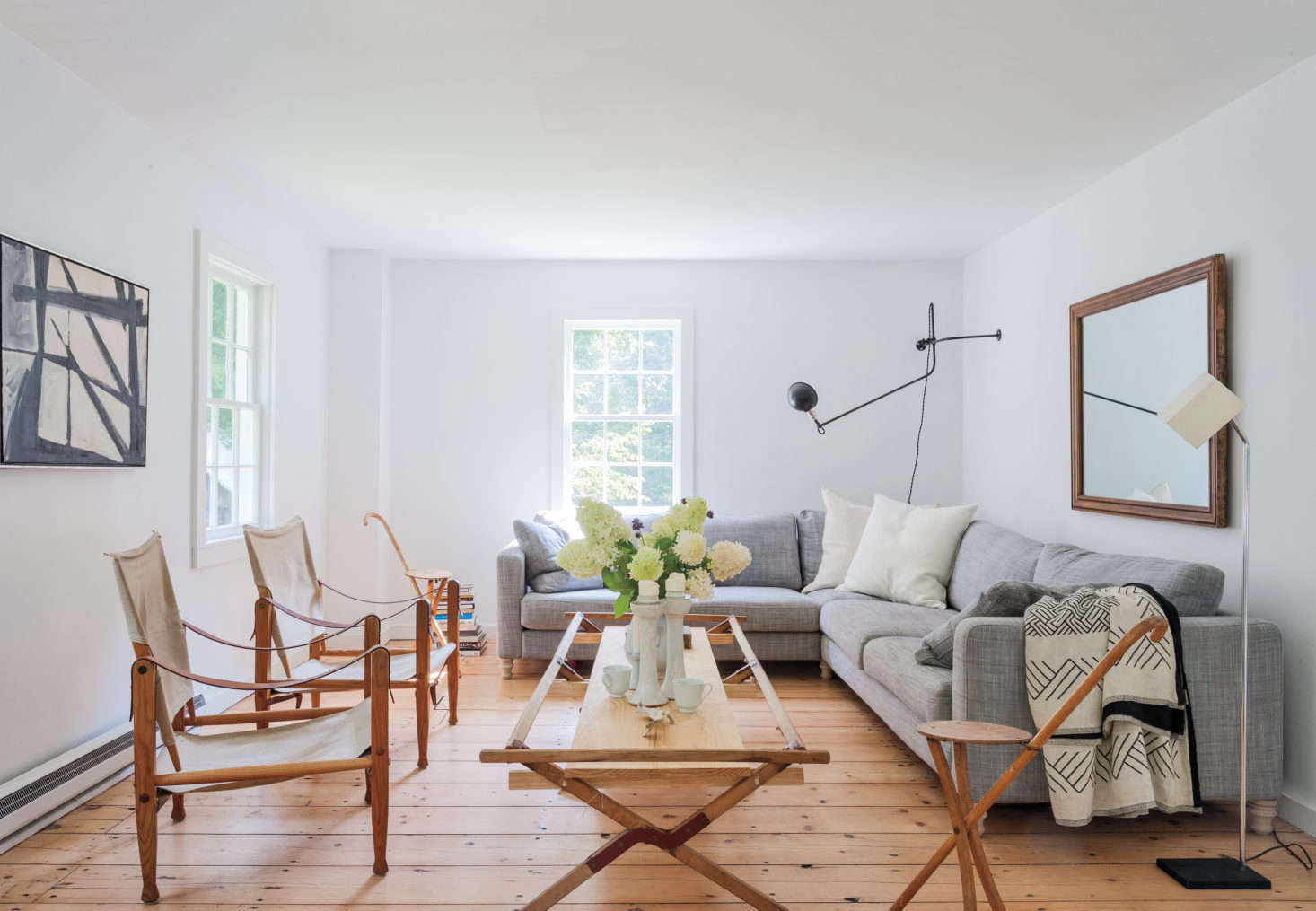 In their Hudson Valley living room, Robert Highsmith and Stefanie Brechbuehler of Workstead maximize a sense of space by using leggy, low-profile furniture and fixtures as well as a mirror over the couch. They also keep the space looking uncluttered by ditching the drapes and the rug. Photograph by Matthew Williams from Remodelista: A Manual for the Considered Home.