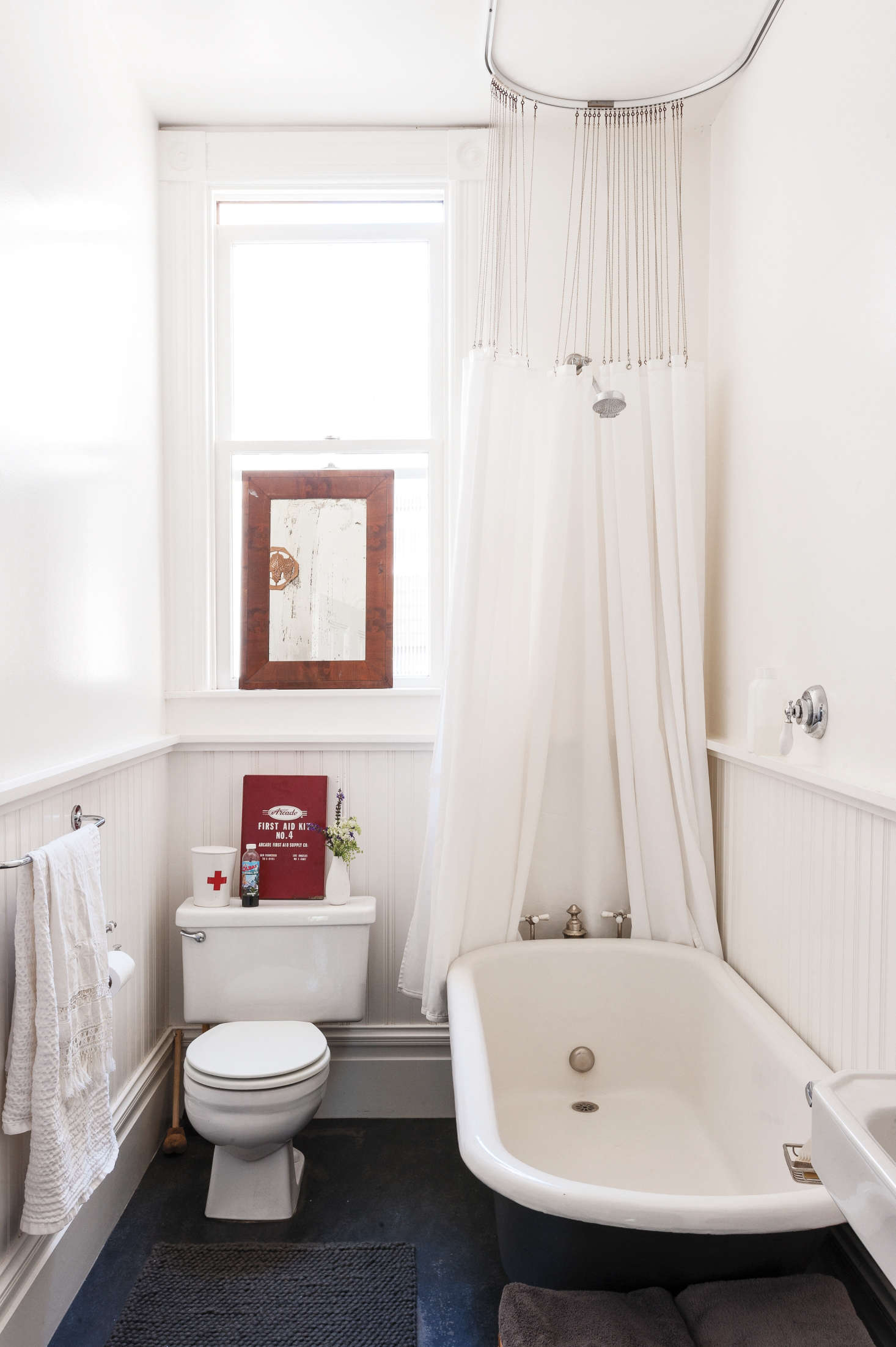 In her wee bath, clothing designer Dagmar Daley ditched her curtains, used all white to maximize the sense of light and air, and she used vertical elements, wainscoting and a shower curtain, to emphasize the height of the room. Photograph by Matthew Williams from Remodelista: A Manual for the Considered Home.