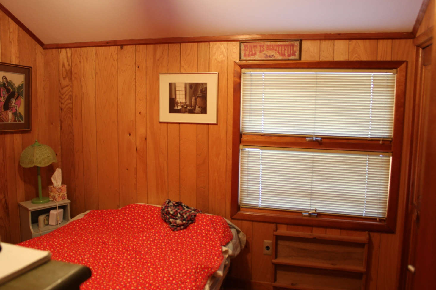 A guest bedroom was covered in dark wood paneling.