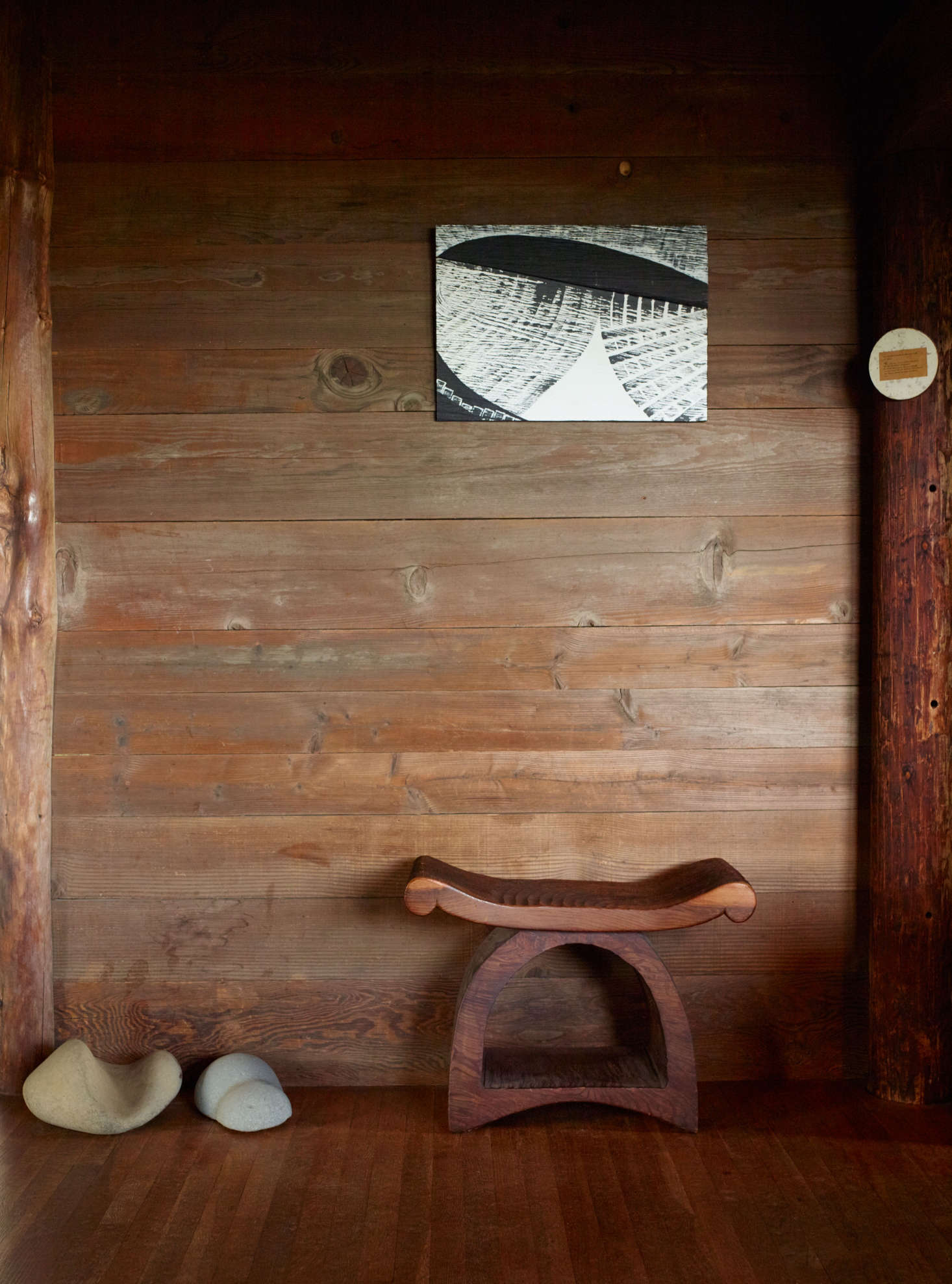 Blunk's painting in black and white mirrors the chainsaw markings on the underlying redwood plank. The flared and curved outlines of the redwood stool echo the silhouettes on a display of river rocks.