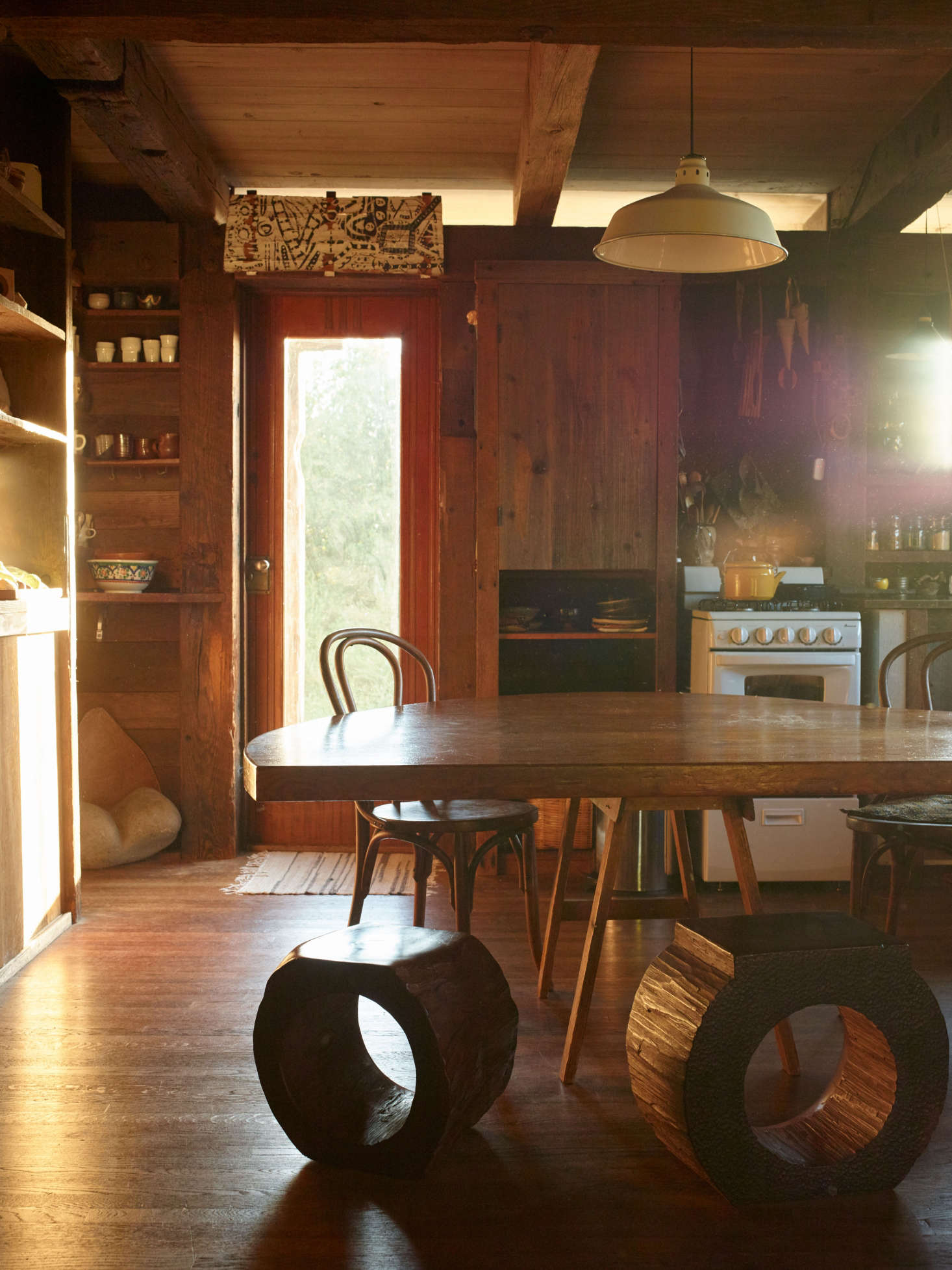 J. B.'s first wife, Nancy Waite, designed and made the kitchen's polygonal table with sawhorse supports. J. B. hollowed redwood chunks with a chainsaw to make the stools. Above the doorway hangs a Blunk abstract artwork, painted on redwood bark.