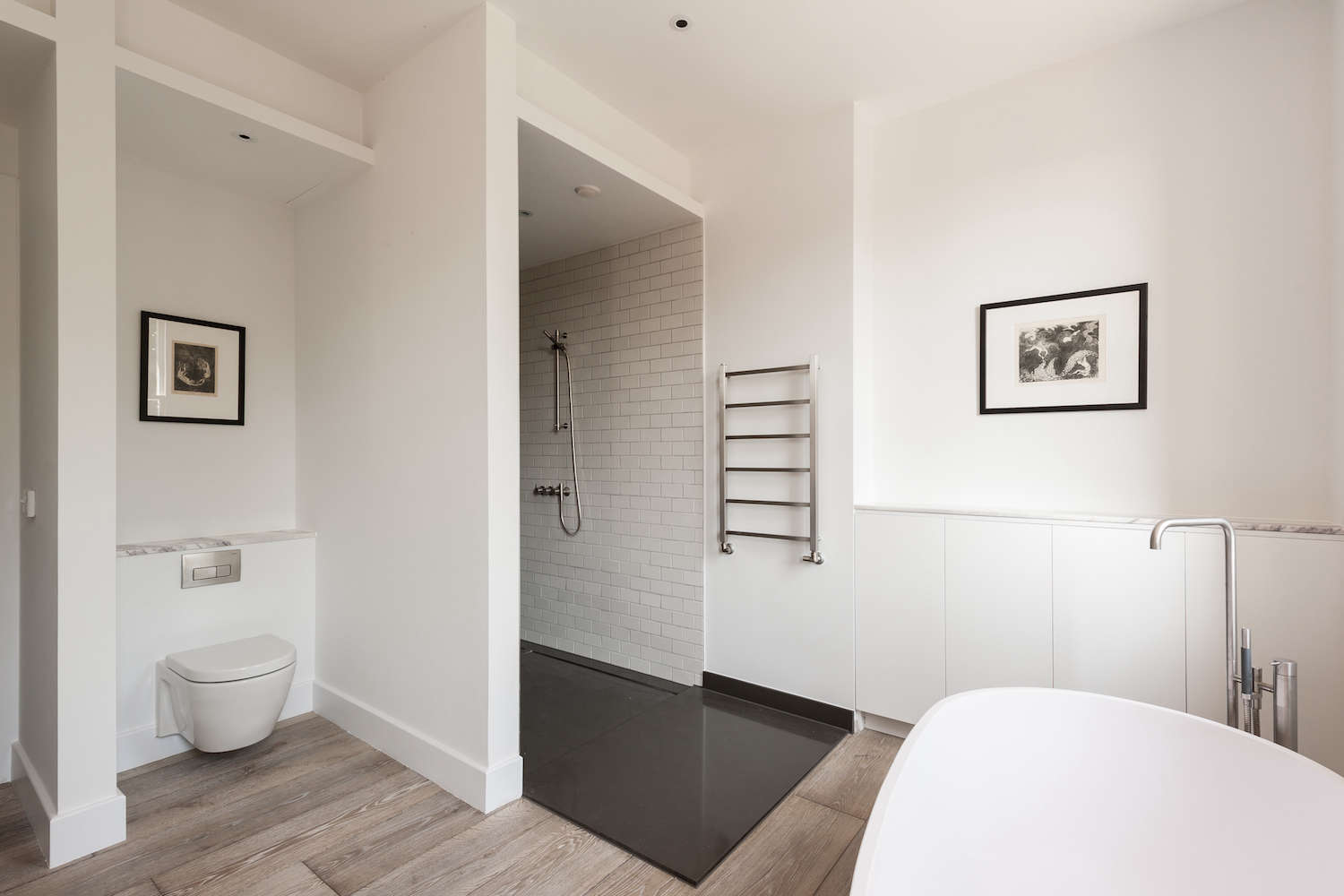 Modern White Bathroom With Wall Hung Toilet And Freestanding Bathtub