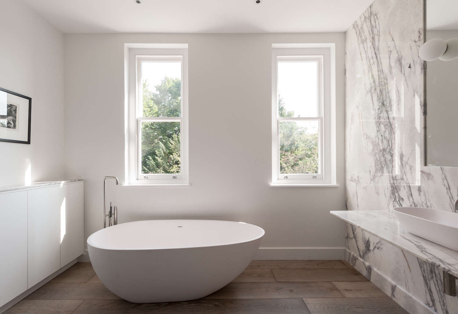 Delightful Modern White Bathroom In UK With Freestanding Bathtub And Marble Slab Wall