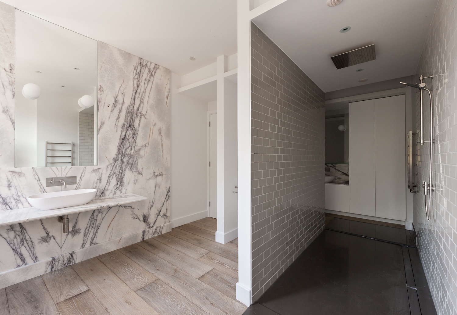 white marble bathroom with slab wall and ceramic wood tile floors