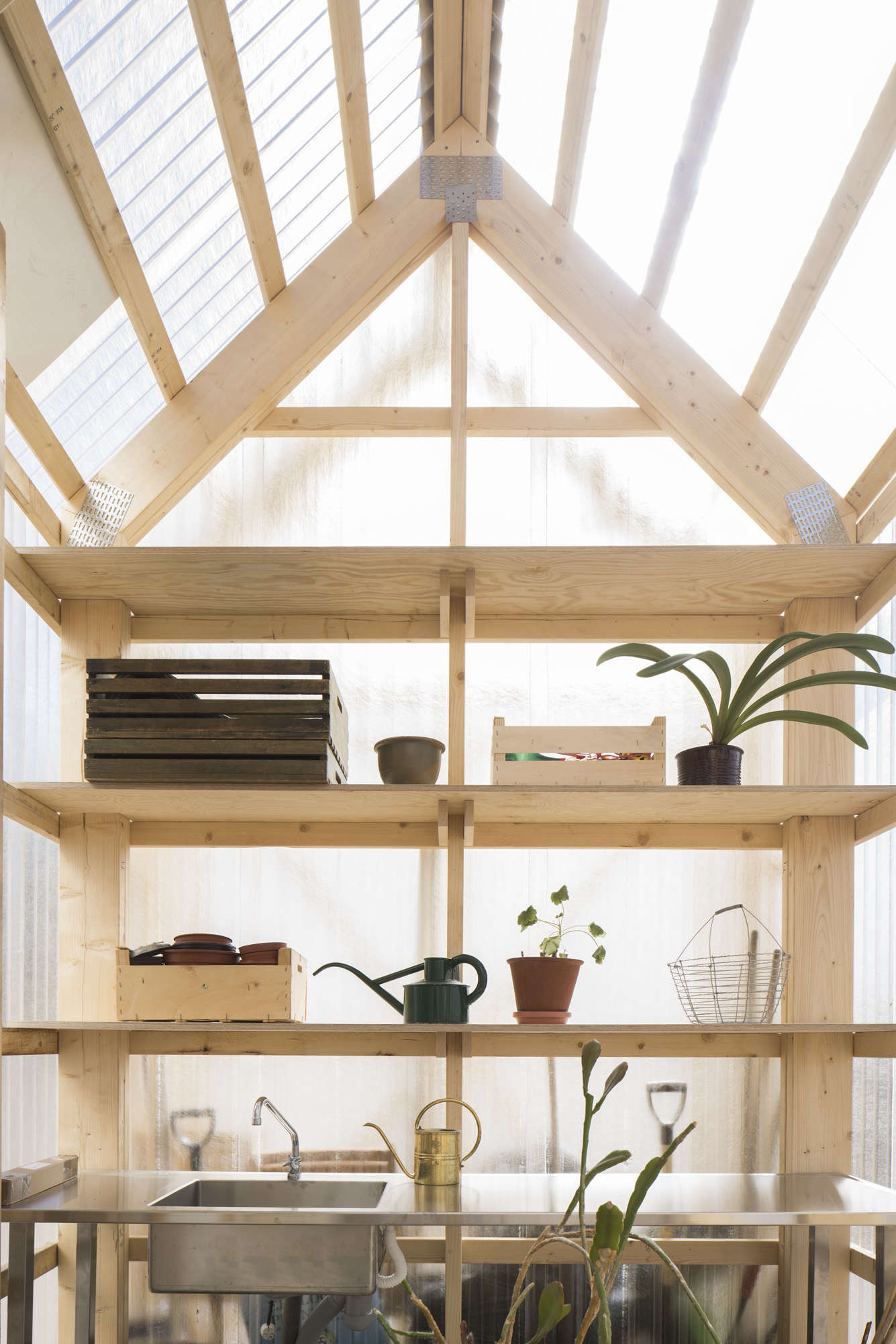 A greenhouse with translucent corrugated polycarbonate walls and exposed wood frame in Forstberg Ling's House for Mother