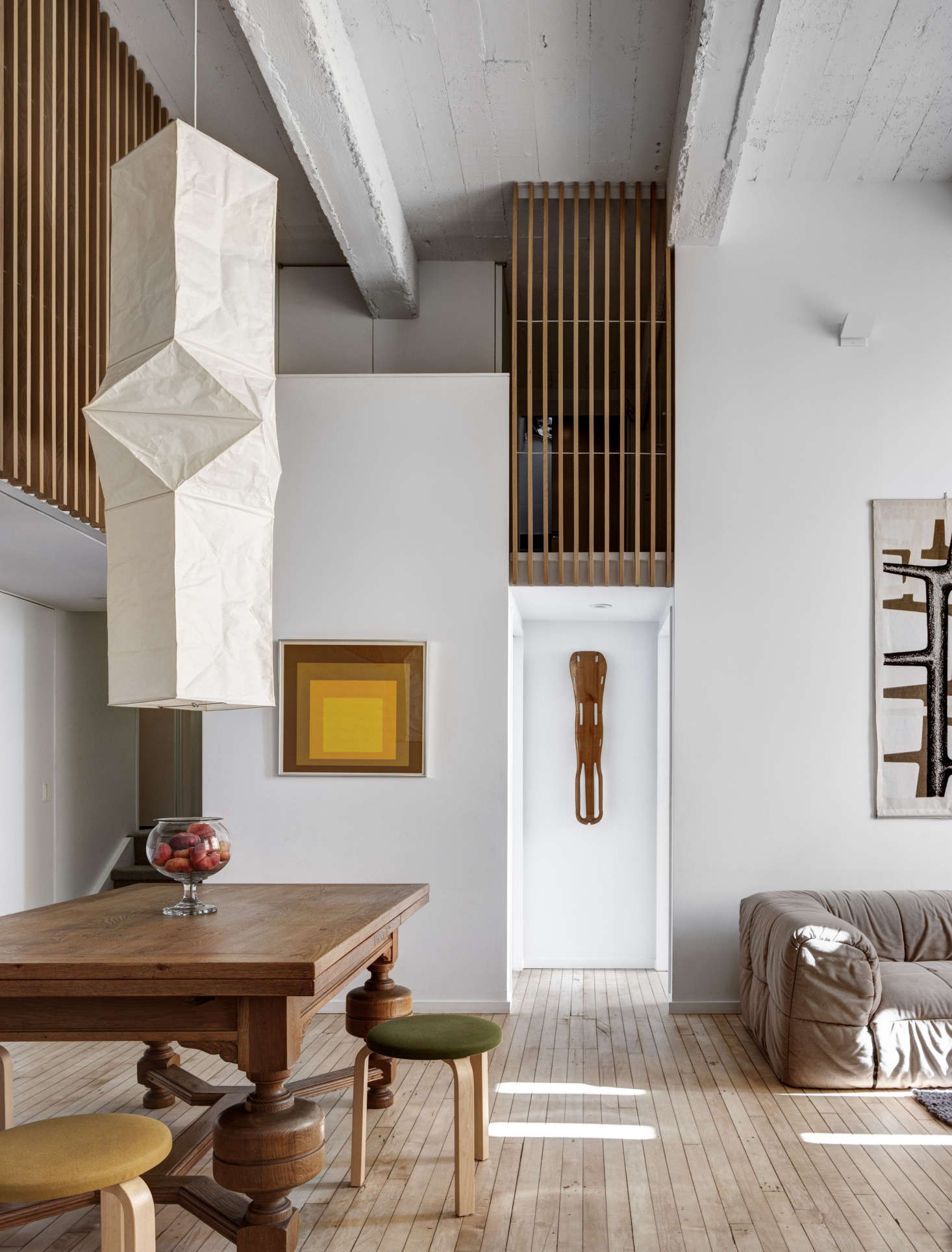 An Akari Ceiling Lamp, Model L5 from the Noguchi Museum Store hangs in the lofty living area of this Brooklyn apartment. Photograph by Bruce Buck, from An Eclectic Apartment Inspired by Japanese Storage Chests in Cobble Hill, Brooklyn.