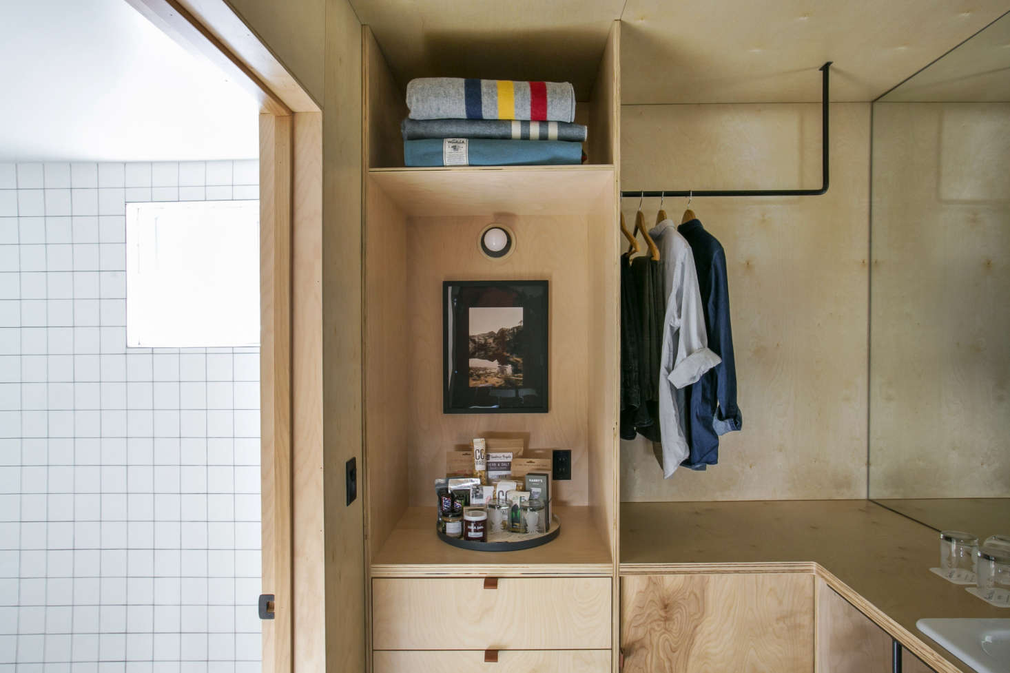 Plywood creates smart storage opportunities in a small hotel bathroom/closet. For more, see Bathroom of the Week: An Economical Plywood Bath in Tahoe.